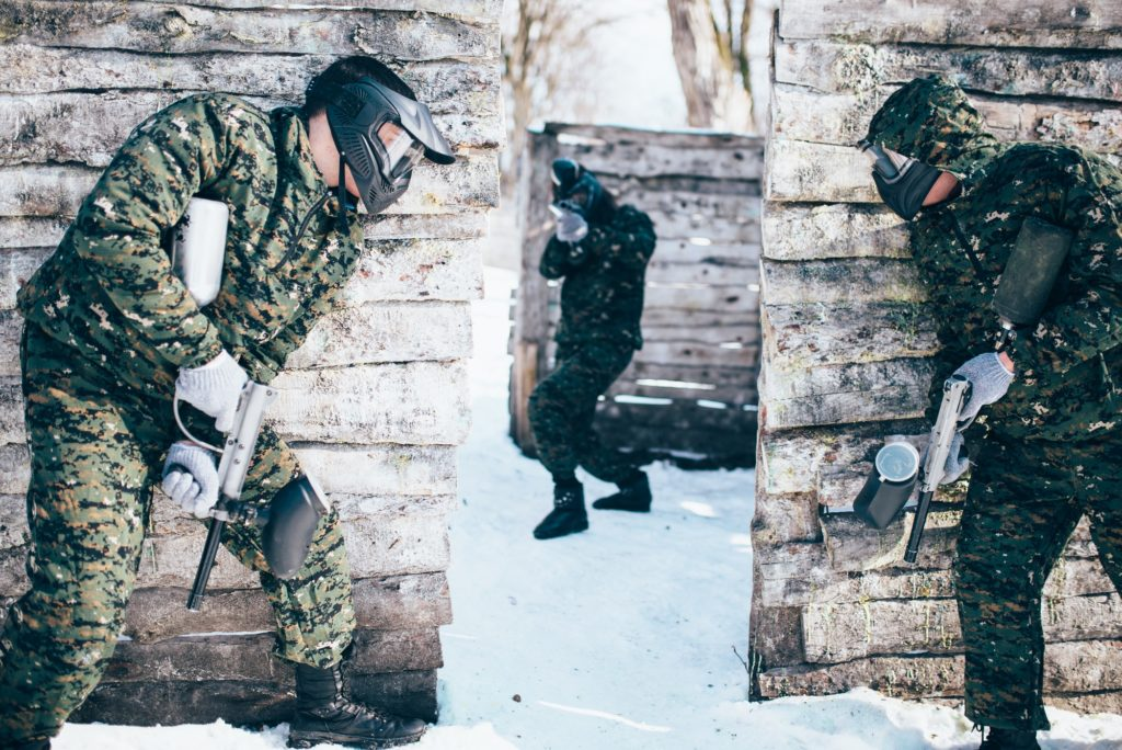 Paintball battle, paintballing in winter forest