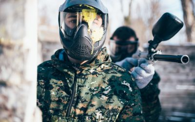 Paintball player in splattered mask, front view